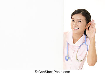 A female nurse place her hand on her ear - Smiling female ...
