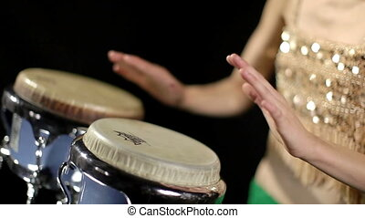 a female percussion drummer performing with bongos, ...
