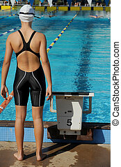 A female relay swimmer waits for her turn to start during a competition.