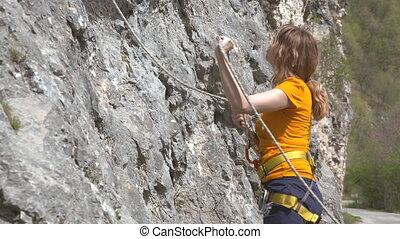 A female rock climber climbs up a rock