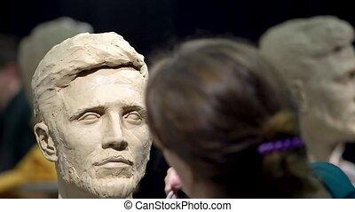 A female sculptor creates a sculpture of a human head. Eye ...