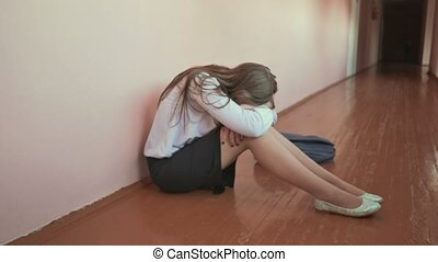 A female student is crying on the floor of a corridor at school.