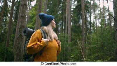 A female traveler in a yellow sweater with a backpack is ...