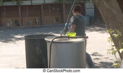 A female volunteer takes water to a bucket at a dog shelter....