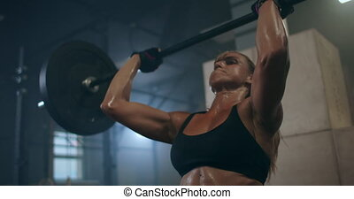 a female weightlifter performs a barbell lift in a dark gym. a woman lifting a heavy bar over her head. High quality 4k footage