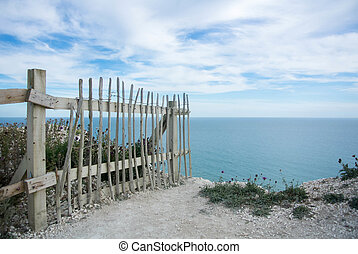 A fence at the cliffs, Seven Sisters country park, England.