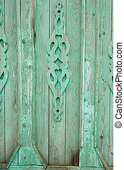 A fence or a green gate that has burned out in the sun. Jewelry made of carved wood.Texture.