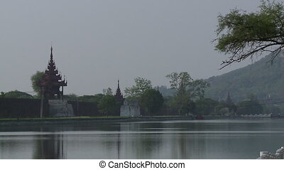 A long shot of a fenced pagoda on front of a waterbody in the city of Mandalay, Myanmar