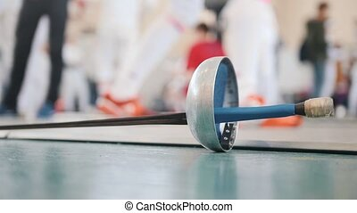 A fencing tournament. A sword lying on the floor while the...