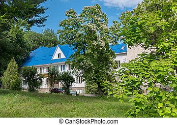 a, ferienhaus, stehende , in, a, schöne , grün, bereich, unter, bäume, mit, a, bank, für, rest, bei, der, grüner rasen, gegen, der, blaues, sky.