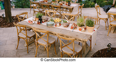 A festive table with fresh flowers in pots in an open area with trees. Wooden chairs in rustic style, snacks on the tables at the buffet table.