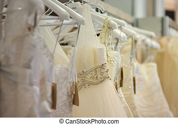 A few beautiful wedding dresses hanging on the stand