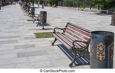 few benches on the embankment with urns