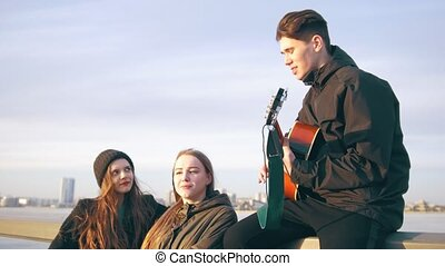 A few happy friends singing with the guitar at the sunset outdoors