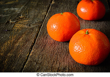 A few mandarins on a wooden background. The cleared fruit.