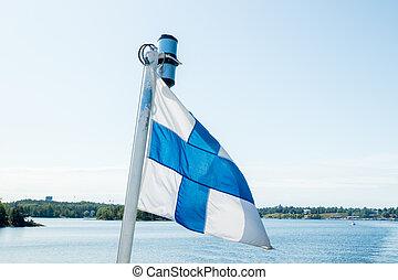 A finnish flag on a boat in the wind on lake Saimaa near the Lappeenranta, Finland