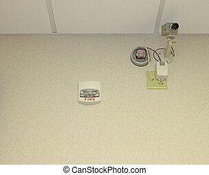 A fire alarm and security or monitoring camera installed on...