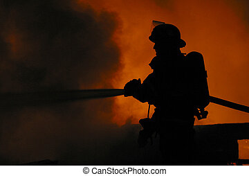 firefighter - a firefighter is silhouetted by a blaze.
