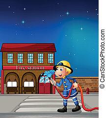 A fireman near a fire station