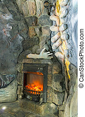 A fireplace made in the wall made of stone. With an unusual setting, the model of a hand lying on it and an unusual stucco on the wall next to it.