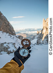 A first-person view of a man's hand with retro compass.