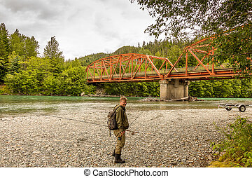A fisherman at the upper Red Highway Bridge on the Kitimat River, Canada