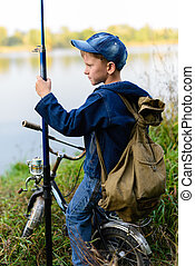 A fisherman boy on the river bank with a fishing rod in his hands. He wants to catch a big fish. He came by bicycle.
