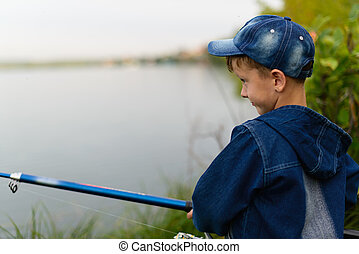 A fisherman boy on the river bank with a fishing rod in his hands. He wants to catch a big fish.