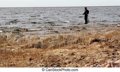A fisherman catching some fish on the sea with some reeds on...