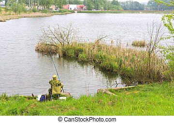 A fisherman fishing on the lake