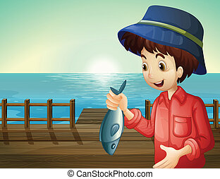 A fisherman holding a fish at the seaport