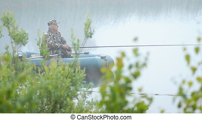 A fisherman in a boat with a fishing rod waiting for the fish. Early morning fog on the lake