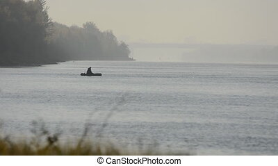 A fisherman in a rubber boat floating on the river....
