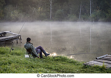 A fisherman on the shore of a small river.