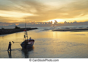 A fisherman with a boat on the ocean shore at sunset. Cha-um, Th