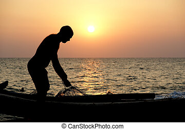 A fisherman with a boat on the ocean shore at sunset. Kerala, India