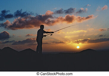 a fisherman with his rod in the sundown