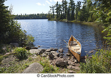 A fisherman's canoe on rocky shore in northern Minnesota lake