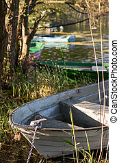 A fishing boat moored to the shore of the lake. Old fishermen's boat prepared for fishing on lakes.