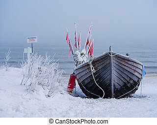A fishing boat on shore of the Baltic Sea in winter.