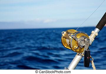A fishing reel set against blue ocean