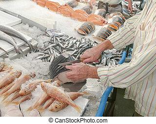 a fishmonger cuts up a fish at athens central market