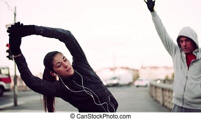 A fit couple runners doing stretching outdoors on the bridge...