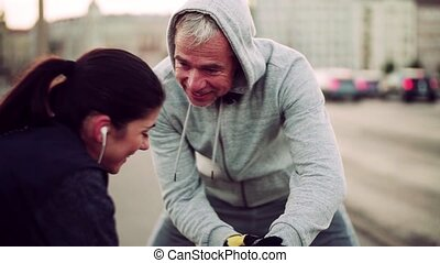 A fit couple runners measuring time outdoors on the streets...