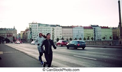 A fit couple running outdoors on the streets of Prague city....