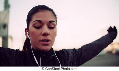 A fit young female runner with earphones doing stretching...