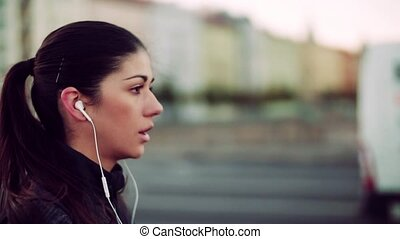 A fit young female runner with earphones running outdoors in...