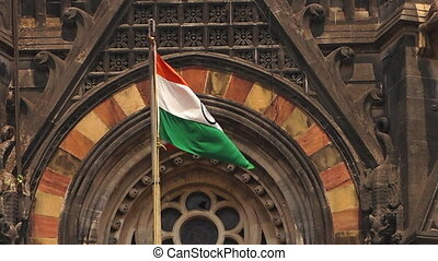 A flag waves in front of an old religious temple - A static...