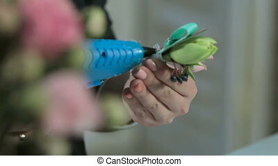 a florist glues a white ribbon on a bouquet