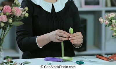 A florist wraps around a flower tulip and cuts a green ribbon on a white table